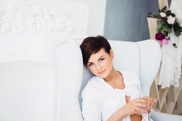 Giovane bruna bella si siede sulla grande sedia bianca