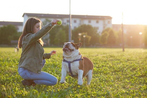 Giovane bruna gioca con il suo bulldog britannico