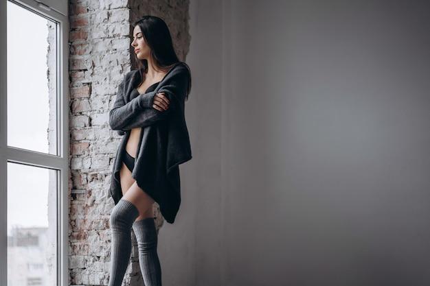 Giovane bruna in intimo nero, ginocchiere tricot e cardigan in piedi vicino alla finestra in una calda coperta.