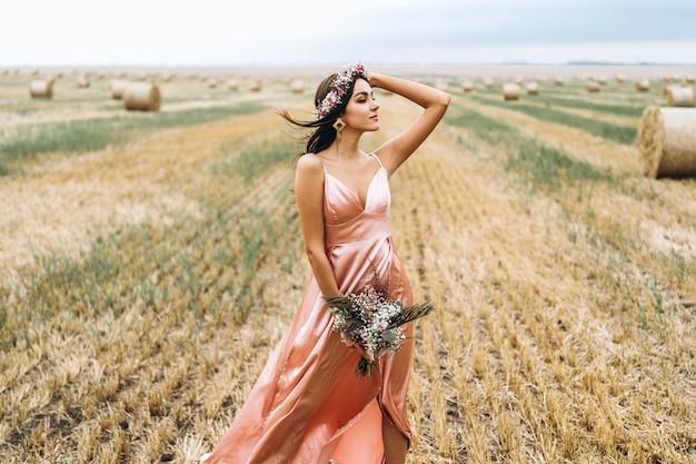 Giovane bruna in un abito di raso rosa in un campo di grano vicino a balle di fieno. una donna ha una corona in testa e tiene in mano un mazzo di fiori di campo