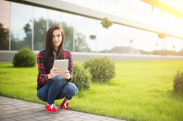 Giovane brunetta womanwith tablet servitù in internet sull'erba