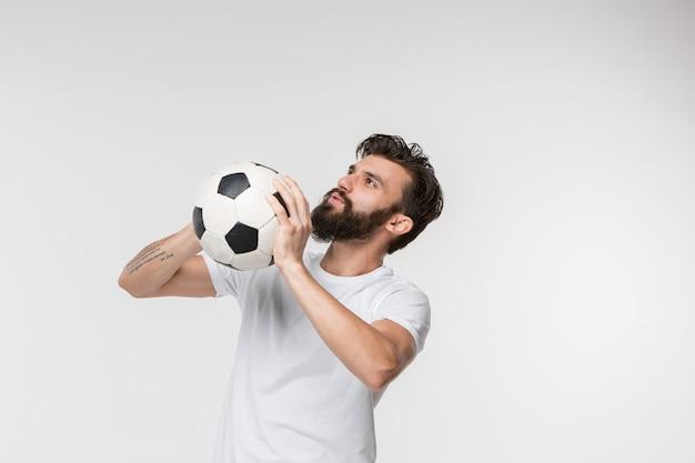 Giovane calciatore con la palla davanti a bianco