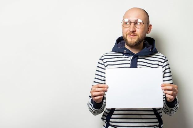 Giovane calvo con la barba con gli occhiali, un maglione con un cappuccio in possesso di un foglio di carta bianco di fronte a lui, guardando di lato su un bianco isolato. copia spazio