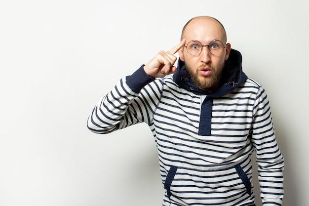 Giovane calvo con la barba in occhiali, un maglione con cappuccio punta un dito al tempio su un bianco isolato. il gesto pensa, fai la scelta giusta