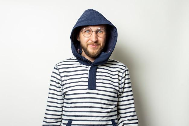 Giovane calvo con la barba in occhiali, un maglione con cappuccio su un bianco isolato. l'uomo nella cappa