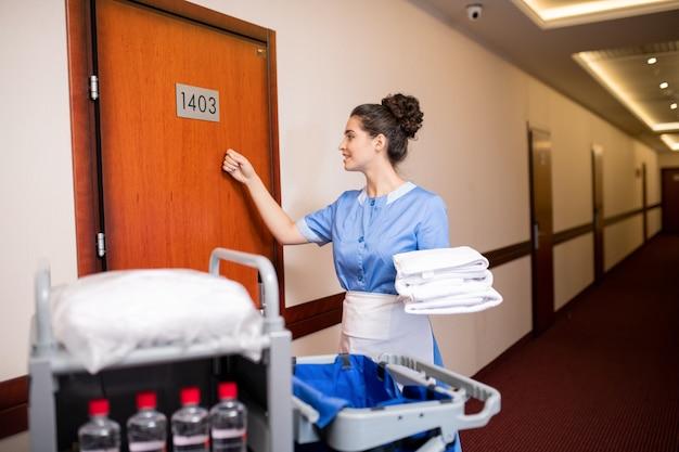 Giovane cameriera contemporanea che bussa a una delle porte di legno per dare asciugamani puliti agli ospiti al mattino