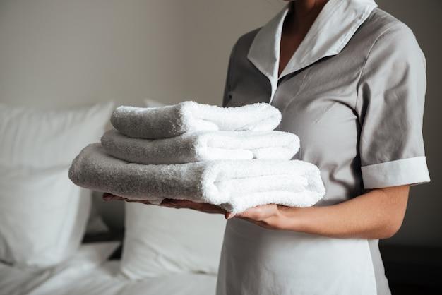 Giovane cameriera d'albergo in piedi e con asciugamani puliti freschi