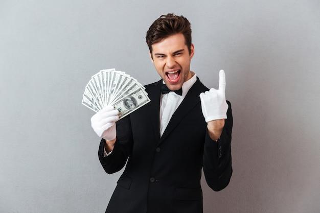 Giovane cameriere di grido che indica mentre tenendo soldi.