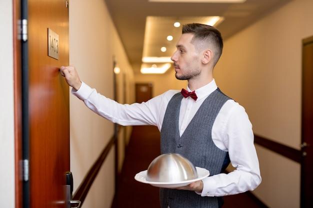 Giovane cameriere elegante che bussa alla porta di legno della camera d'albergo mentre tiene il cibo sulla cloche per uno degli ospiti