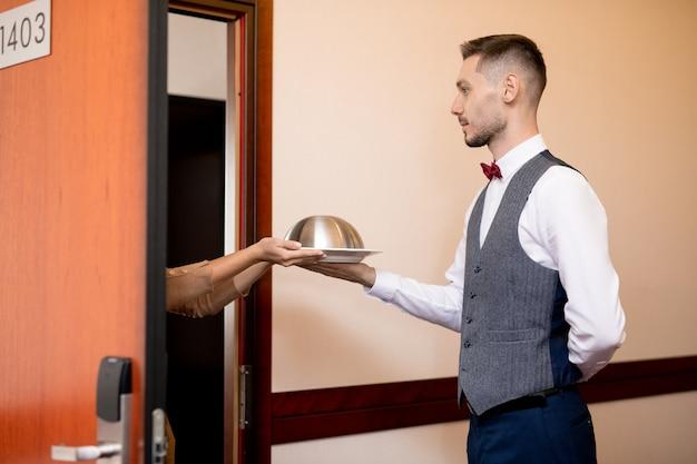 Giovane cameriere serio passando cloche con il cibo a uno degli ospiti dell'hotel mentre si trovava vicino alla porta aperta