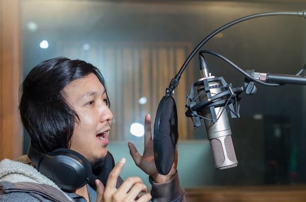 Giovane cantante asiatico registrando una canzone con il microfono in studio musicale