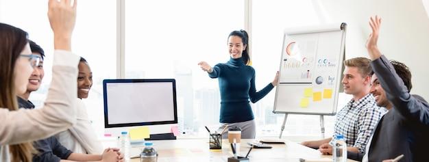 Giovane capo asiatico della donna di affari che chiede l'opinione nella riunione