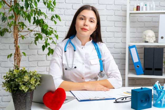 Giovane cardiologo medico femmina seduto alla sua scrivania e il suo lavoro