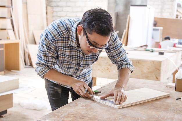 Giovane carpentiere che misura e che segna il bordo di legno
