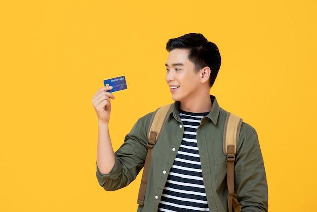 Giovane carta di credito turistica asiatica della tenuta dell'uomo