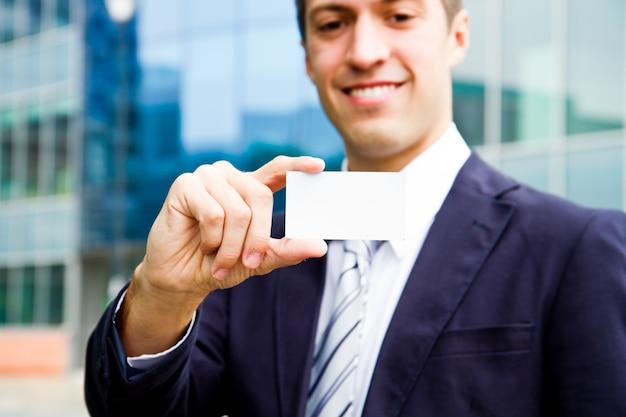 Giovane carta di visita della tenuta dell'uomo d'affari a disposizione e condizione in