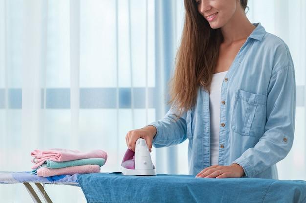 Giovane casalinga felice che riveste di ferro dopo la lavanderia sull'asse da stiro