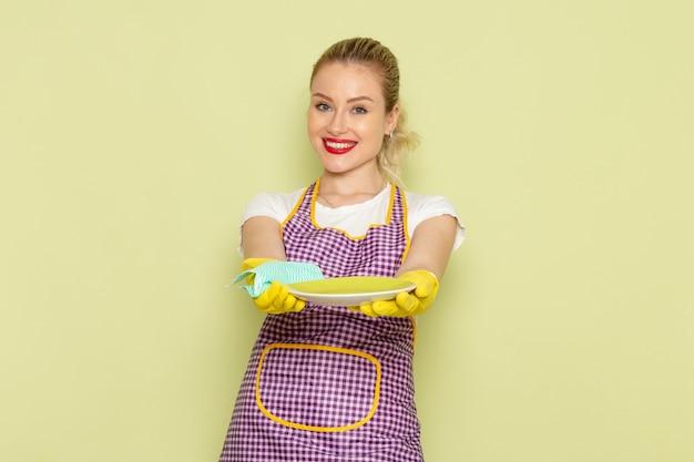 Giovane casalinga in camicia e guanti gialli mantello viola piatti di essiccazione sul verde