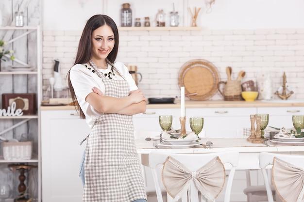 Giovane casalinga sul fondo della cucina. cucina donna a casa. femmina che cucina con lo spazio della copia.