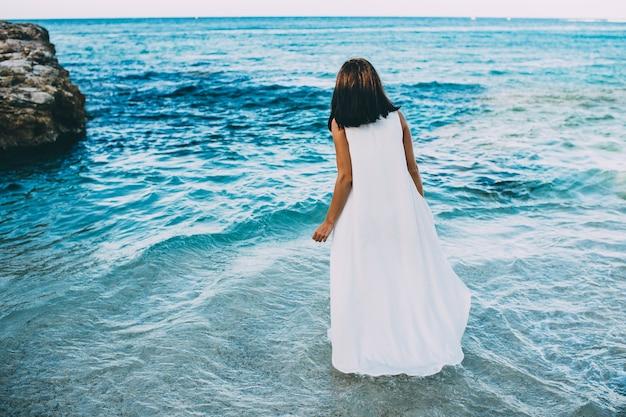 Giovane castana sexy in acqua blu in un vestito bianco sulla spiaggia in grecia