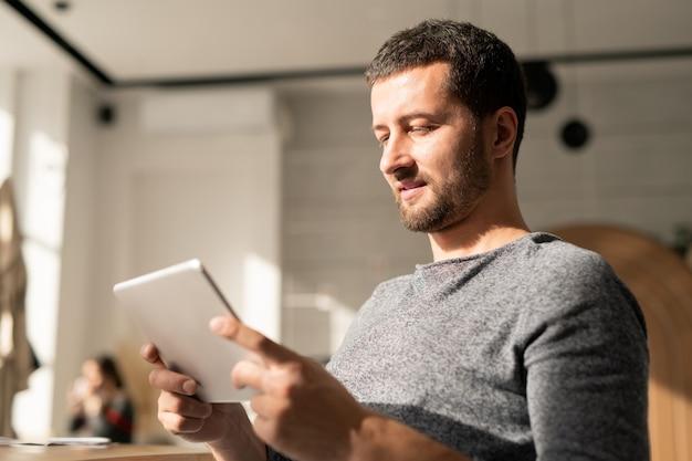 Giovane casual con tavoletta digitale che comunica tramite chat video o naviga in rete a piacimento