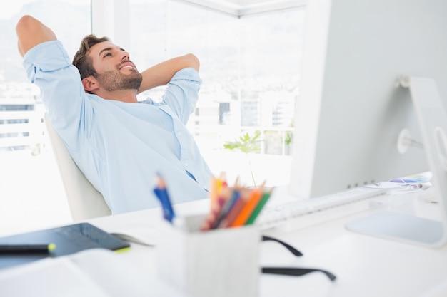 Giovane casuale che riposa con le mani dietro la testa in ufficio