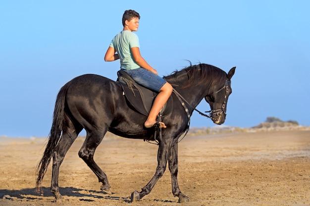 Giovane cavaliere sulla spiaggia