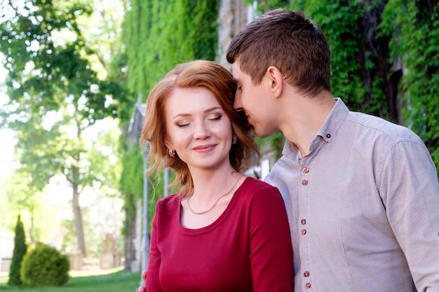 Giovane che abbraccia la donna abbastanza giovane di redhead