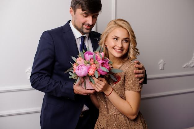 Giovane che abbraccia la sua donna con il mazzo di fiori e guardando verso il basso