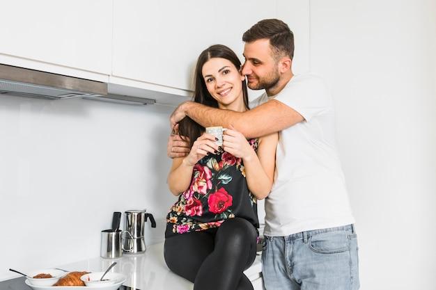 Giovane che abbraccia la sua fidanzata tenendo in mano la tazza di caffè