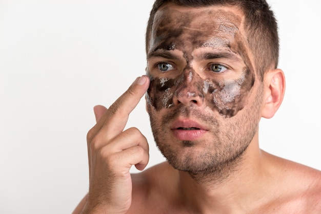 Giovane che applica maschera nera sul suo fronte contro il fondo bianco