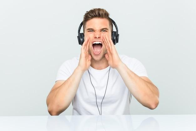 Giovane che ascolta la musica con le cuffie che grida eccitato alla parte anteriore