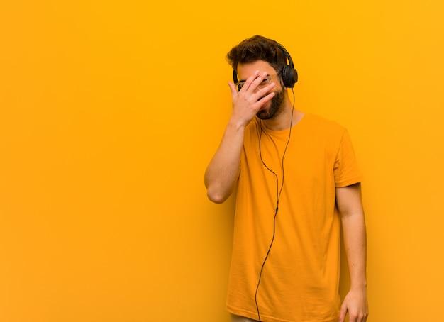 Giovane che ascolta la musica imbarazzata e che ride allo stesso tempo