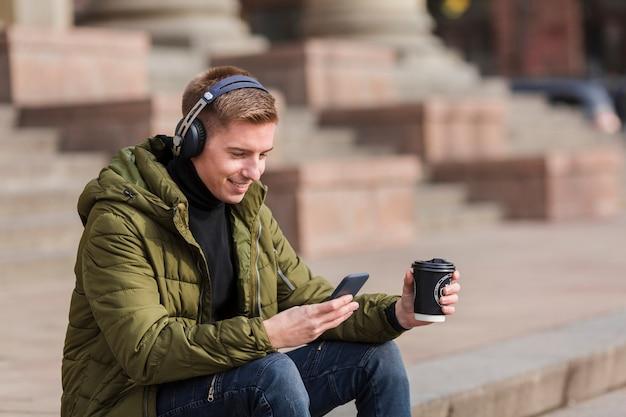 Giovane che ascolta la musica sulle cuffie fuori