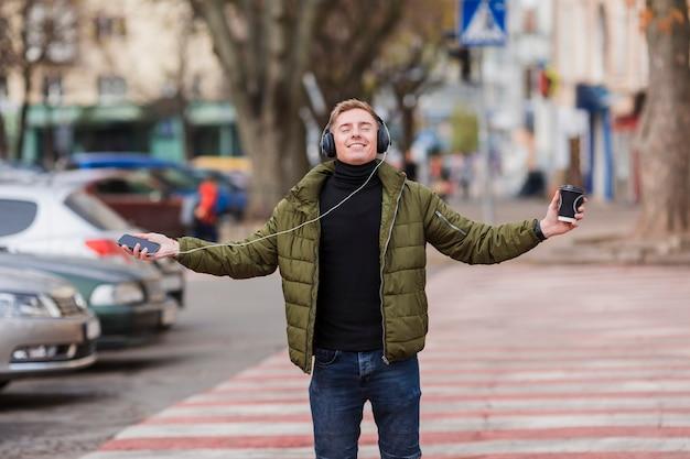 Giovane che ascolta la musica sulle cuffie per le strade