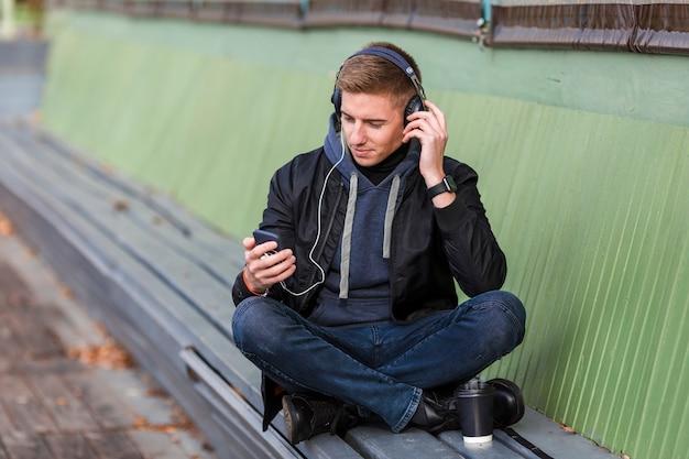 Giovane che ascolta la musica sulle cuffie su un banco