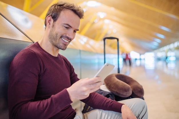 Giovane che aspetta facendo uso del telefono cellulare all'aeroporto con una valigia