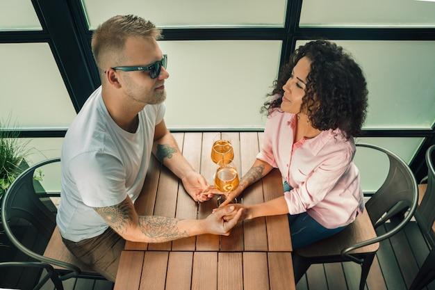 Giovane che bacia la mano di sua moglie mentre presenta la proposta di matrimonio