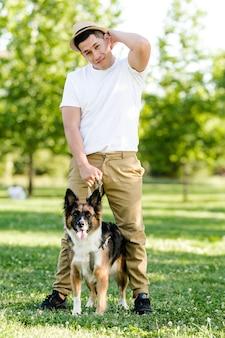 Giovane che cammina con il suo cane nel parco