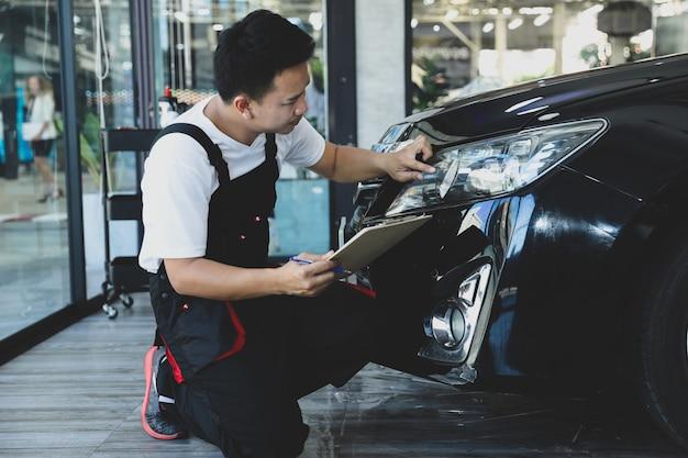 Giovane che controlla l'automobile del faro nella lista di controllo del camion di manutenzione preventiva di concetto.