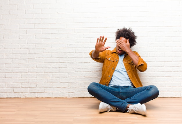 Giovane che copre il viso con la mano e mettendo l'altra mano in alto per fermare la fotocamera, rifiutando foto o immagini seduti sul pavimento a casa