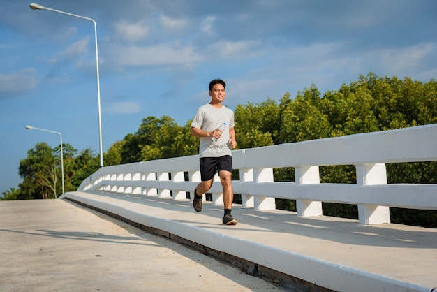 Giovane che corre all'aperto sulla strada al ponte