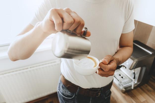 Giovane che cucina il caffè a casa con macchina per il caffè automatica.