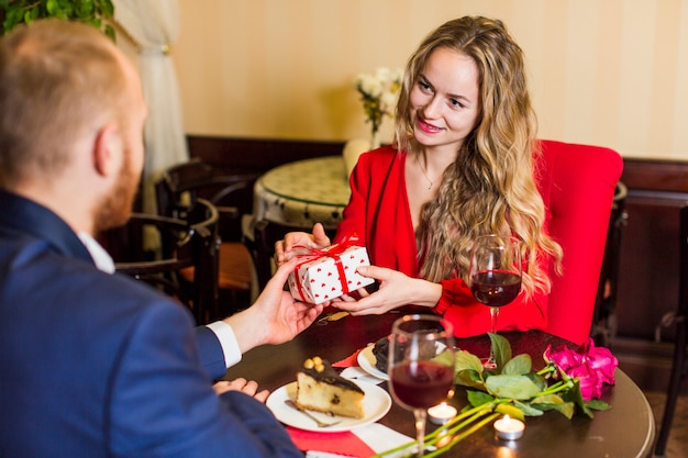 Giovane che dà il contenitore di regalo alla donna alla tavola in ristorante