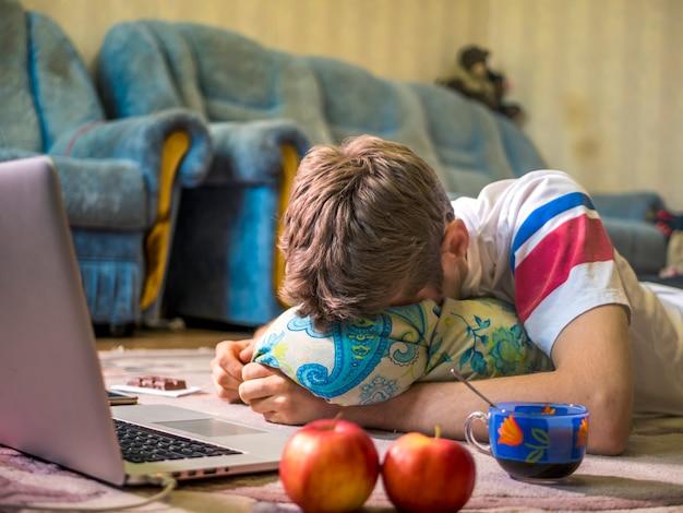 Giovane che dorme davanti al computer portatile mentre trovandosi sul tappeto del pavimento