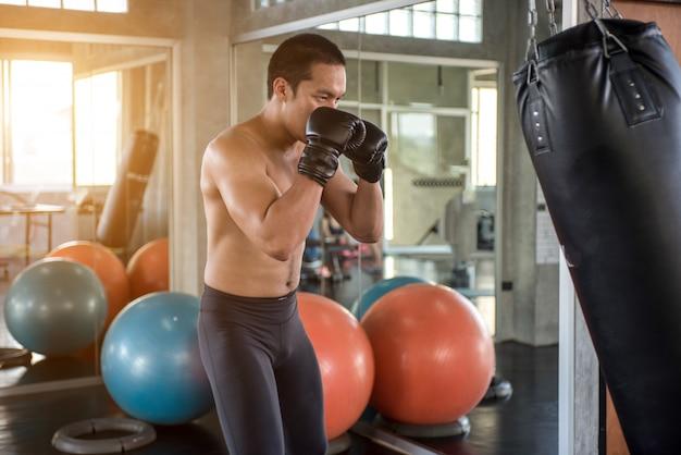 Giovane che fa allenamento di boxe in palestra, indossa guanti da boxe e colpisce il sacco da boxe.