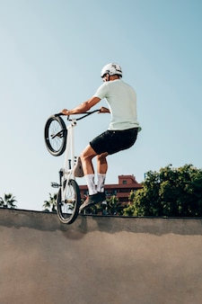 Giovane che fa i trucchi sulla sua bicicletta