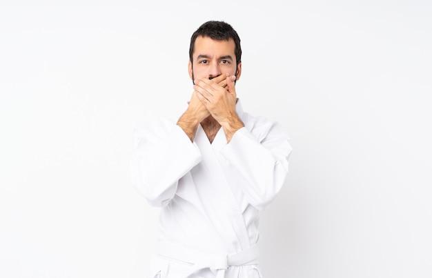 Giovane che fa karatè sopra la bocca bianca isolata della copertura del fondo con le mani