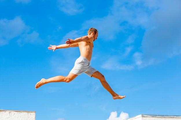 Giovane che fa salto del parkour sui precedenti del cielo blu il giorno di estate soleggiato