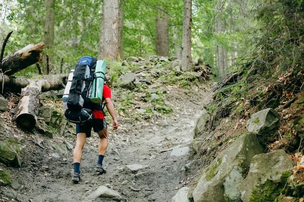 Giovane che fa un'escursione con uno zaino nella foresta